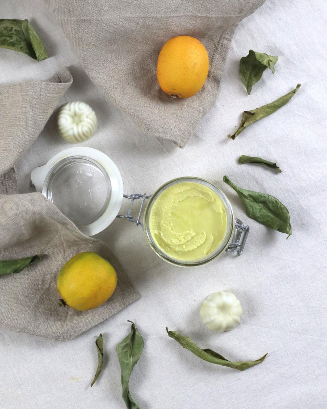 Bodybutter in einem Glas mit Zitronen und kleinen Seifen